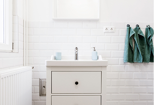 Simple white bathroom sink with subway tiles and radiator.