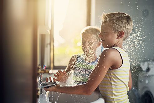 Two boys playing with spraying water.